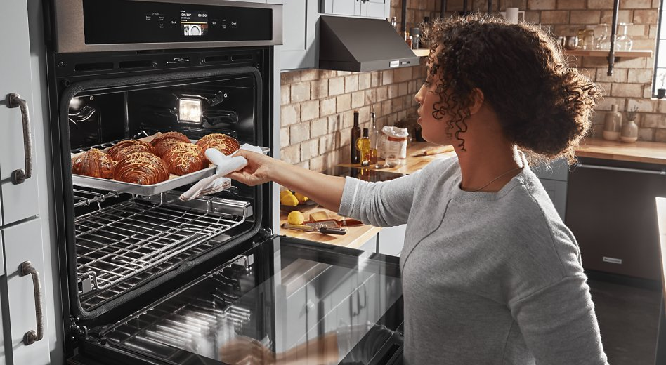 Woman removing fresh-baked croissants from oven