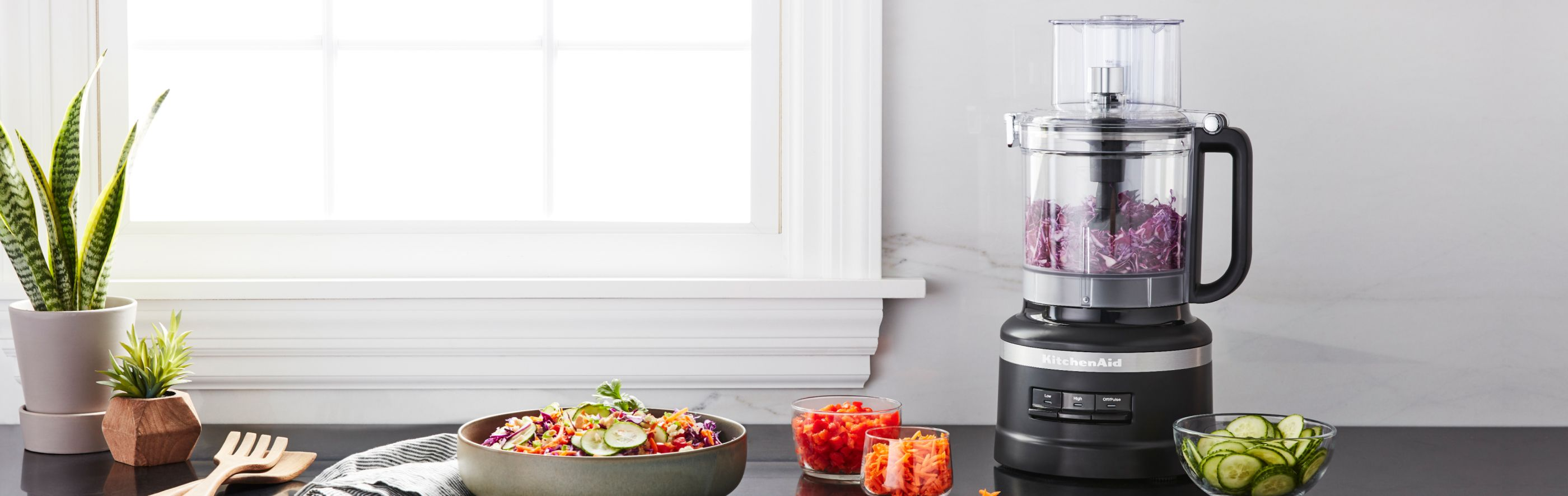 KitchenAid® food processor on a counter among chopped and sliced vegetables.