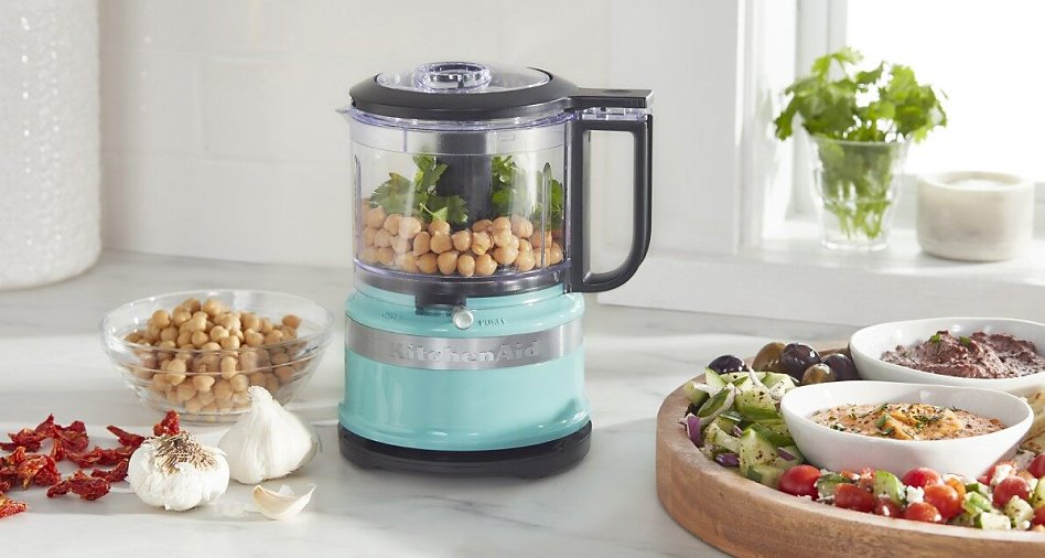 Blue KitchenAid® food chopper filled with hummus ingredients next to a platter of crudités