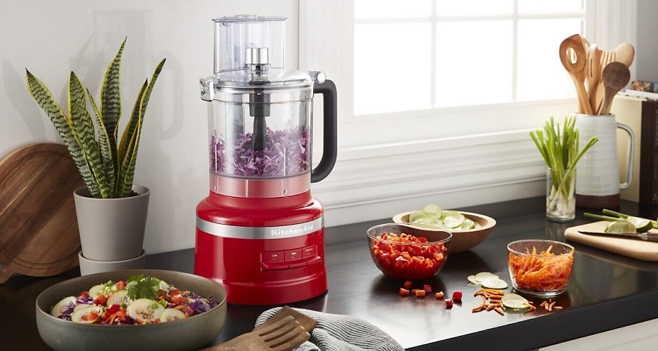 Red KitchenAid® food processor work bowl filled with shredded cabbage.