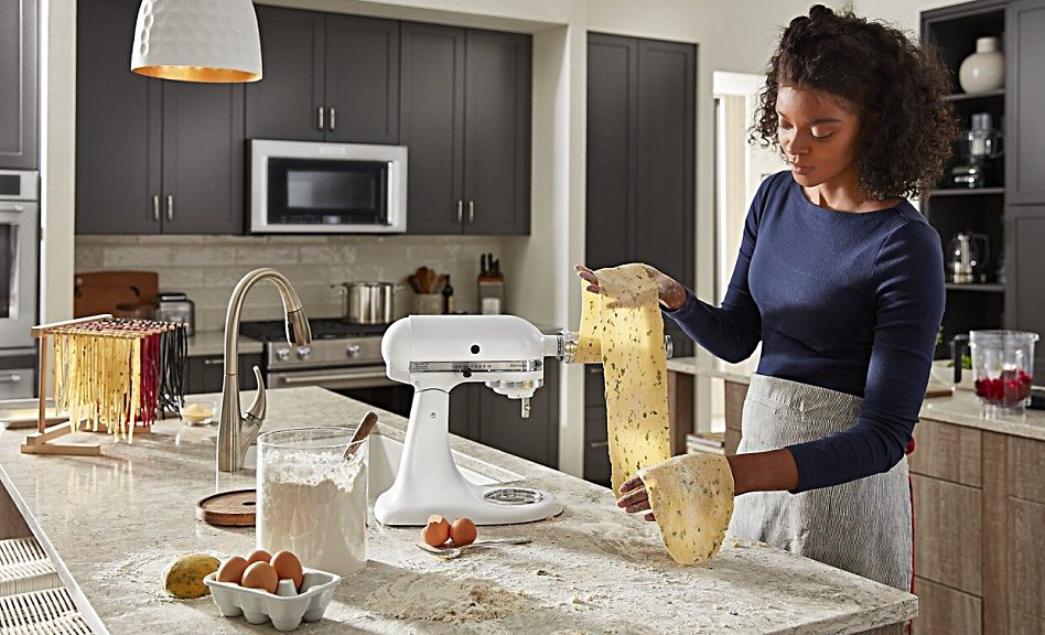 Woman rolling pasta with KitchenAid® stand mixer attachment