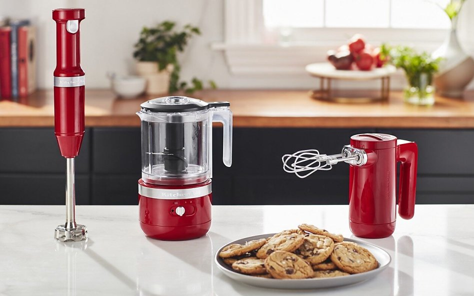 Red KitchenAid® cordless collection appliances on counter with cookies