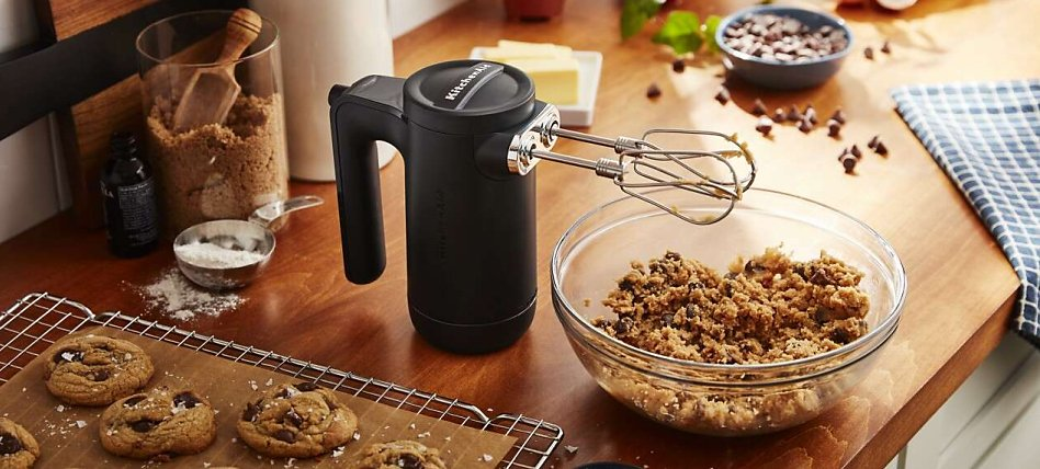 Black cordless hand mixer with cookie dough and baked cookies