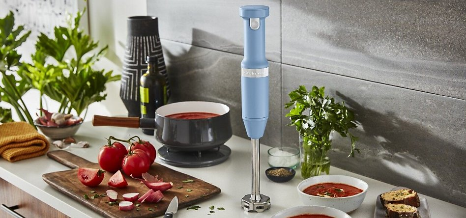 Blue Velvet cordless hand blender on countertop with tomato soup