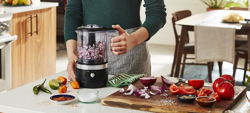 Woman chopping onions with a black cordless food chopper