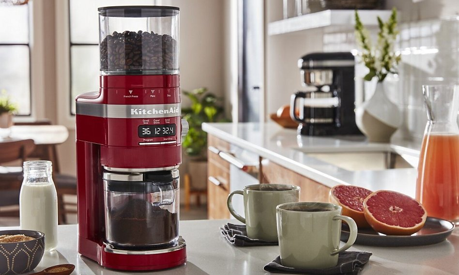 Red burr coffee grinder on counter with coffee cups and grapefruit