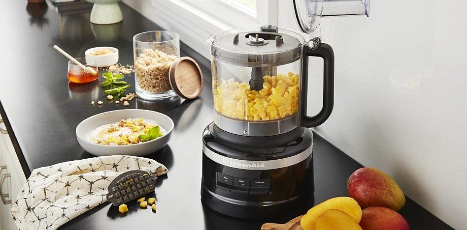 Black food processor on a counter with chopped mango in the work bowl