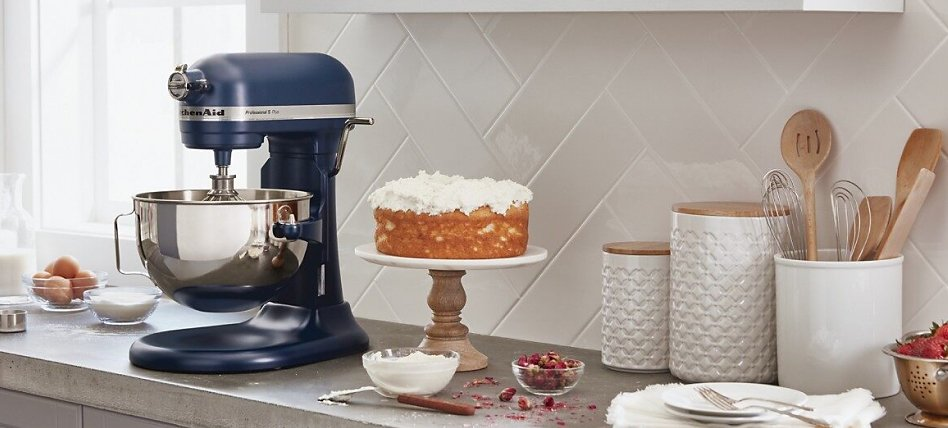 Blue bowl-lift stand mixer on counter next to cake