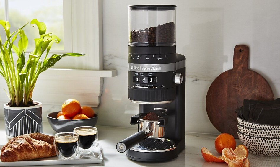 Black burr coffee grinder filling a portafilter on counter with brewed espresso