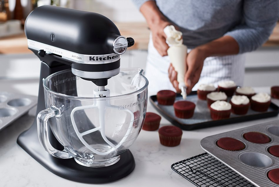 Black stand mixer with glass bowl and man frosting cupcakes in background
