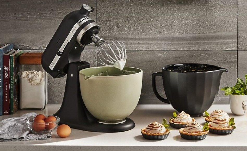 Black stand mixer on counter with 4 ceramic mixing bowls
