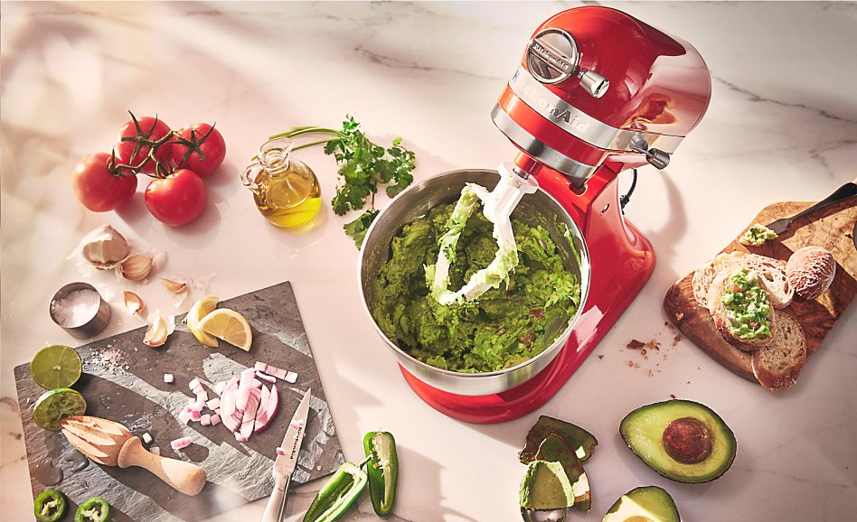 Red stand mixer from above with guacamole and ingredients