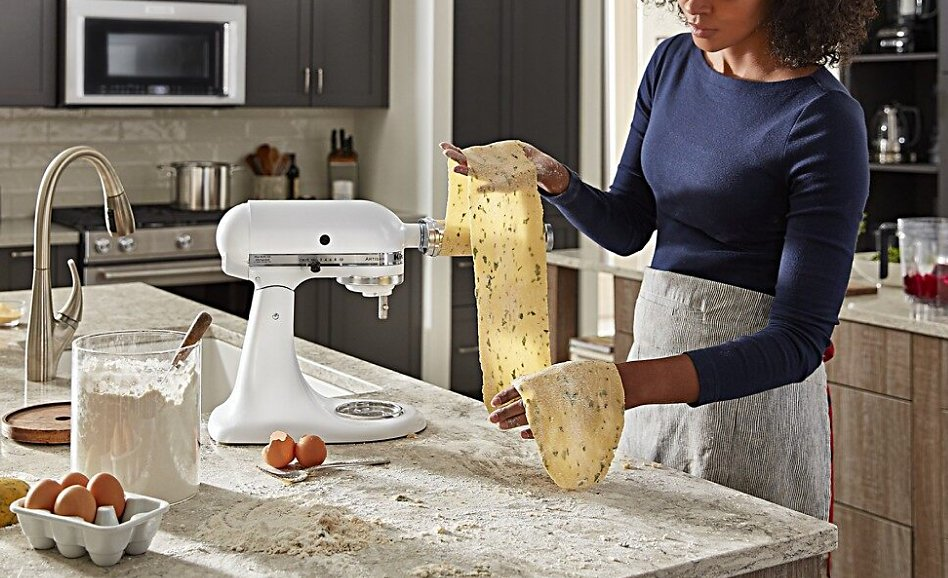 Woman using white stand mixer to roll homemade pasta with an attachment