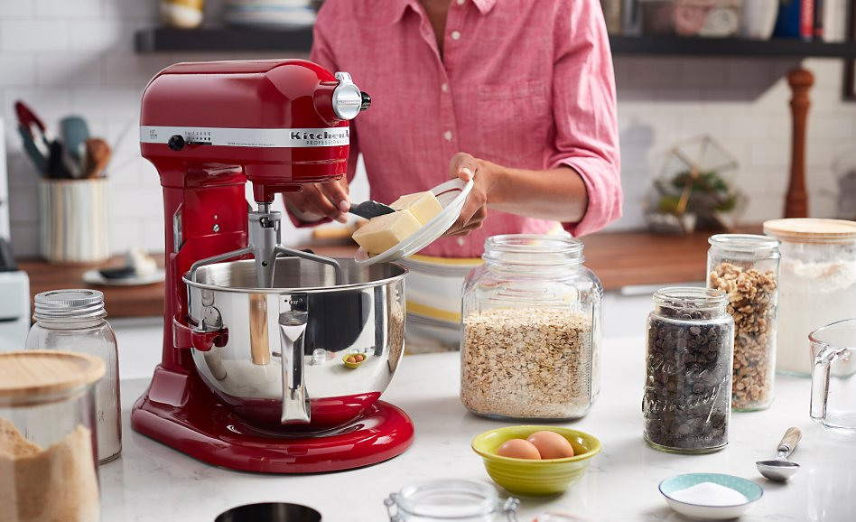 Red bowl-lift stand mixer on counter with jars of ingredients, woman adding butter to bowl