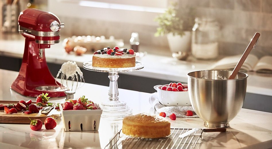 KitchenAid® stand mixer next to a cake, bowl of whipped cream and carton of berries.