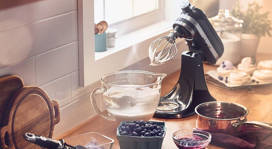 KitchenAid® stand mixer on countertop with whipped cream in a glass mixer bowl next to fresh berries.