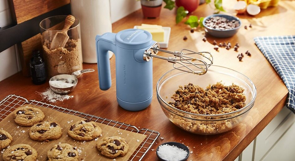 KitchenAid® hand mixer with bowl of cookie dough and wire rack with  fresh baked cookies.