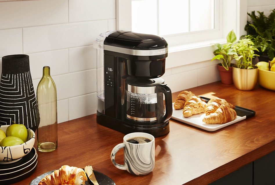 KitchenAid® auto drip coffee maker on counter with coffee and croissants