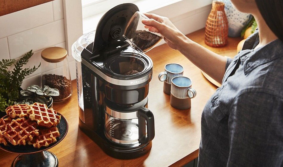 Woman pouring grounds into auto drip coffee maker