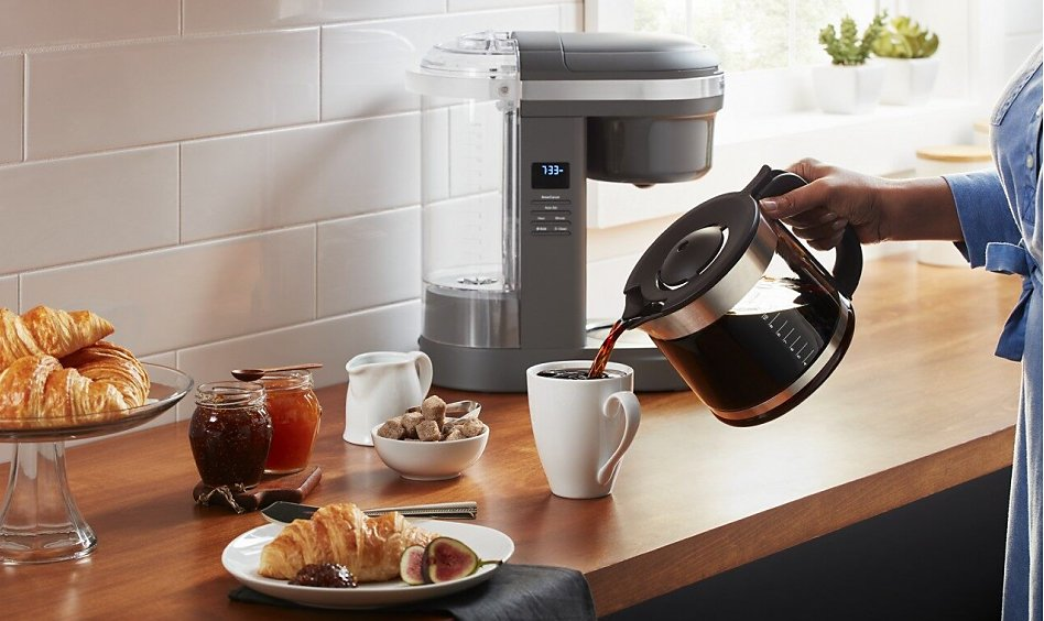 Woman pouring coffee from carafe with auto drip coffee maker in background