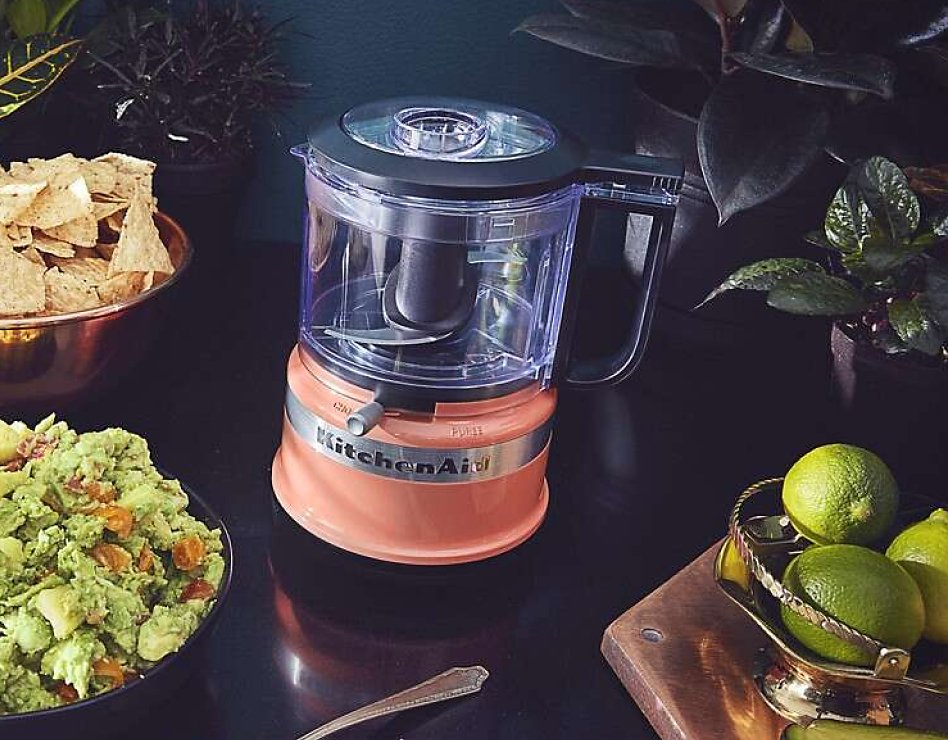 Coral food chopper next to bowl of guacamole and limes
