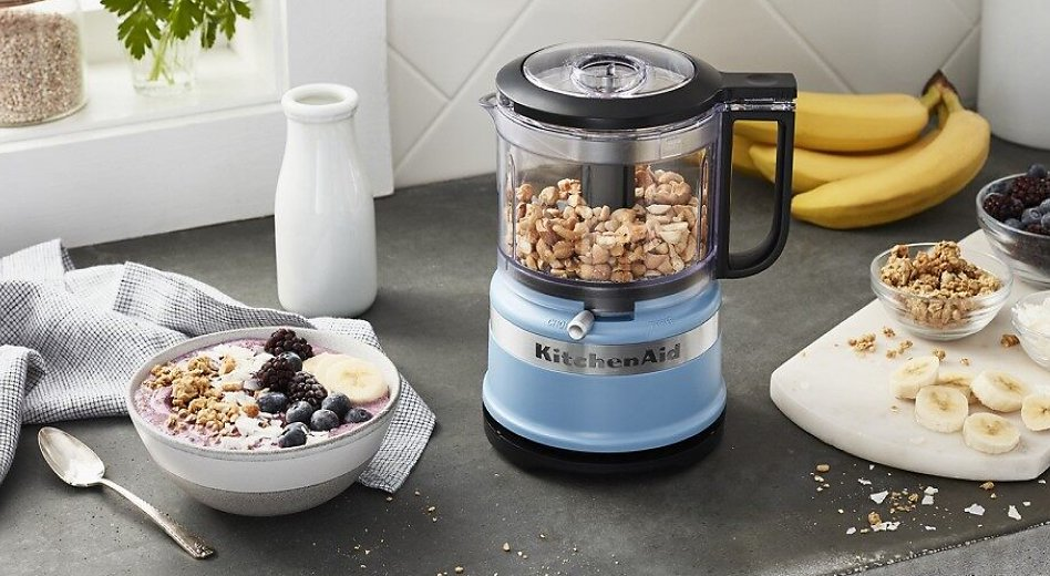 Small blue food chopper chopping nuts next to a smoothie bowl