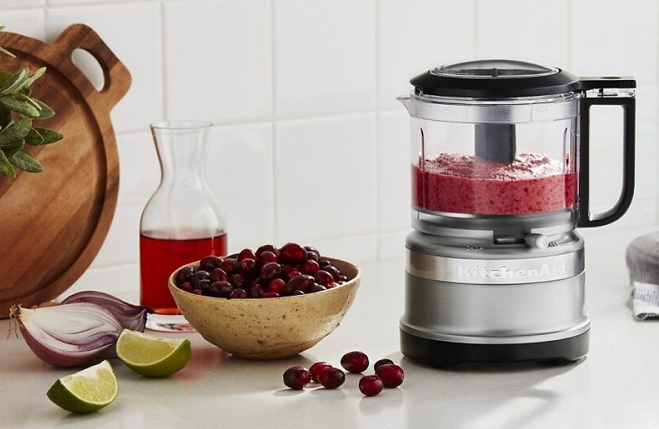 Food processor filled with a fruit purée on a counter