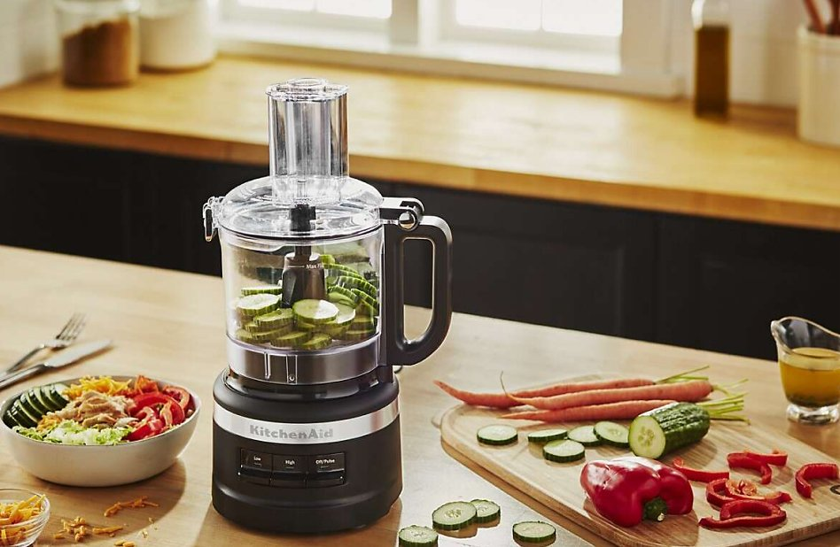 Mid-sized black food processor slicing cucumbers on a countertop