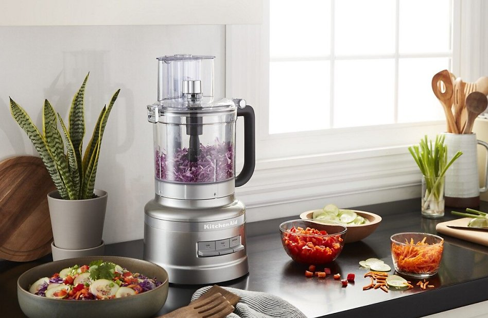 Silver 13-cup food processor on counter with sliced and shredded vegetables