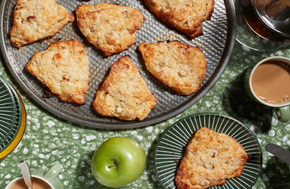 Baked scones in a pan next to an apple and a cup of coffee