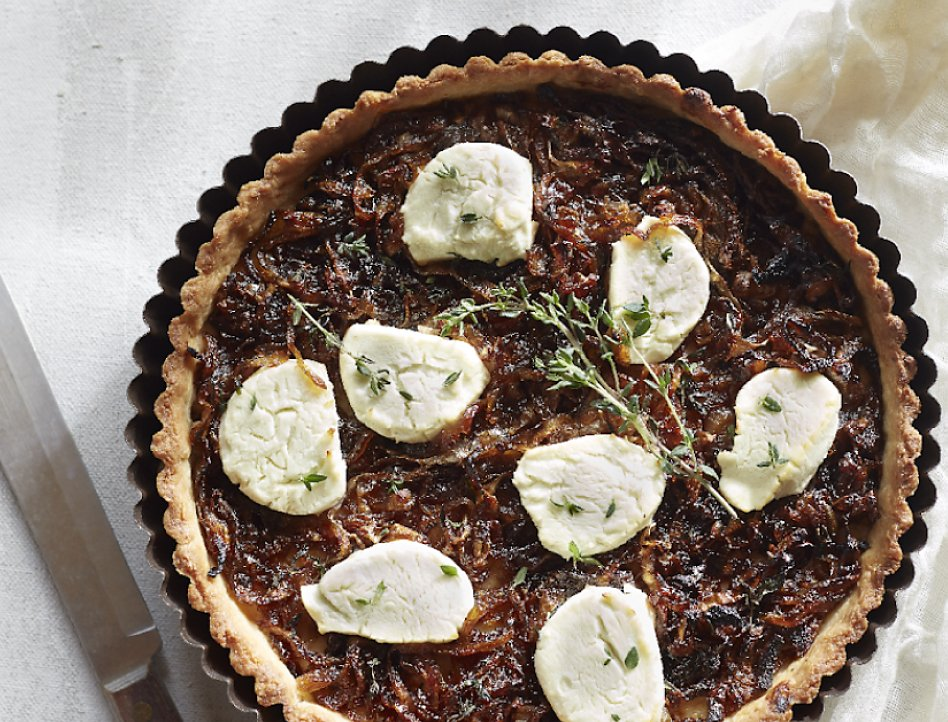Caramelized onion goat cheese tart on table next to knife