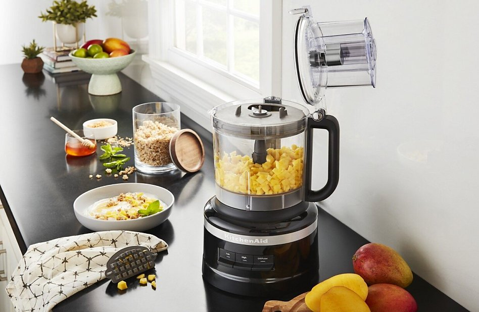 Large-sized black food processor with diced mango on counter with other ingredients