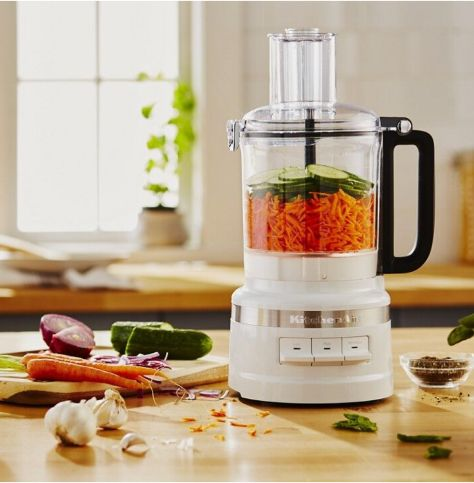 Food processor filled with carrots and cucumbers