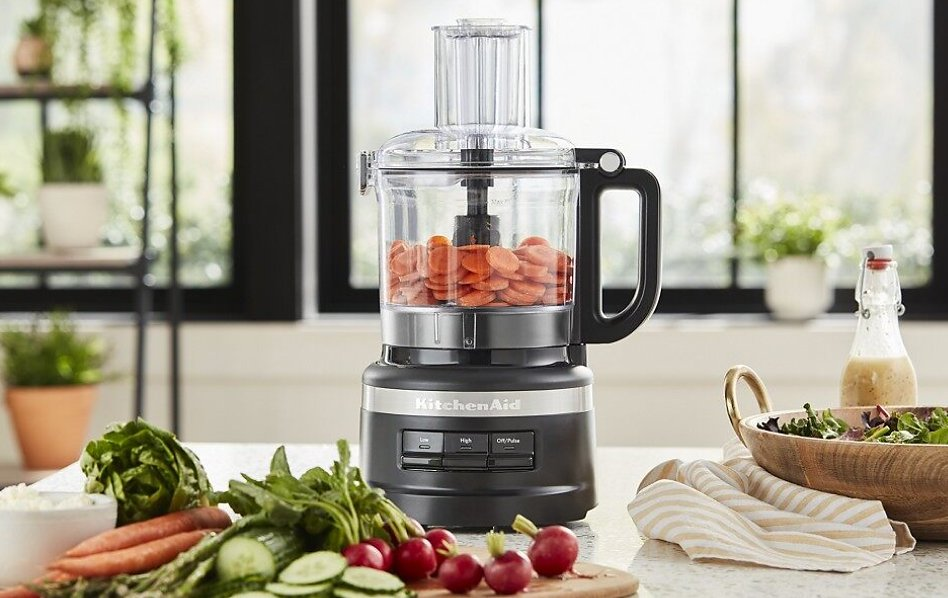Black KitchenAid® food processor with sliced carrots and vegetables in bright kitchen