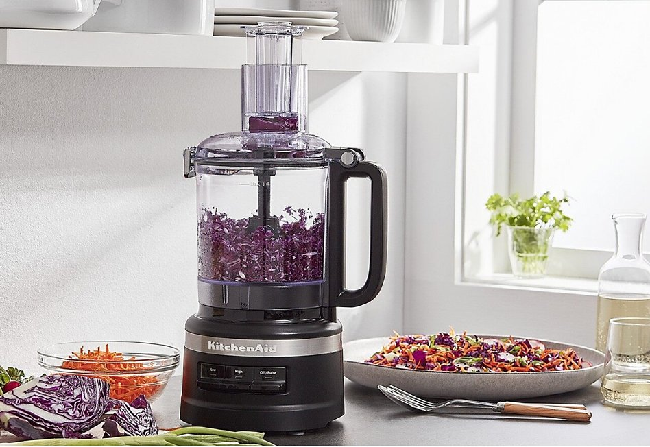 Black food processor with shredded red cabbage on counter with salad