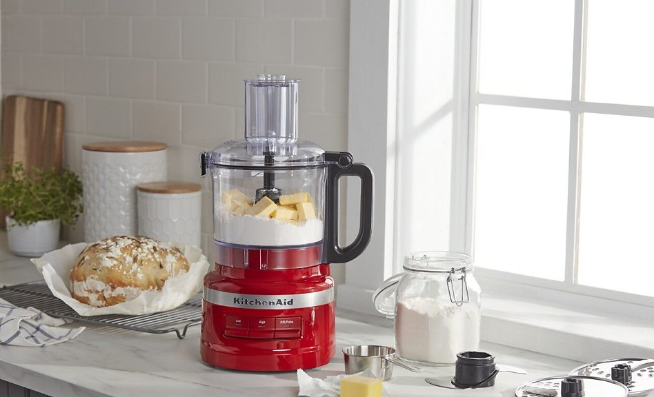 Red food processor with butter and flour next to a loaf of bread