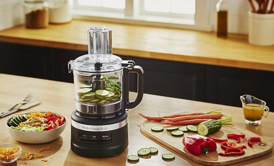 Black food processor with sliced cucumbers surrounded by vegetables and a salad