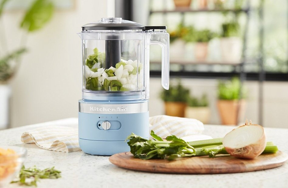 Blue food chopper with chopped celery and onions in bright kitchen