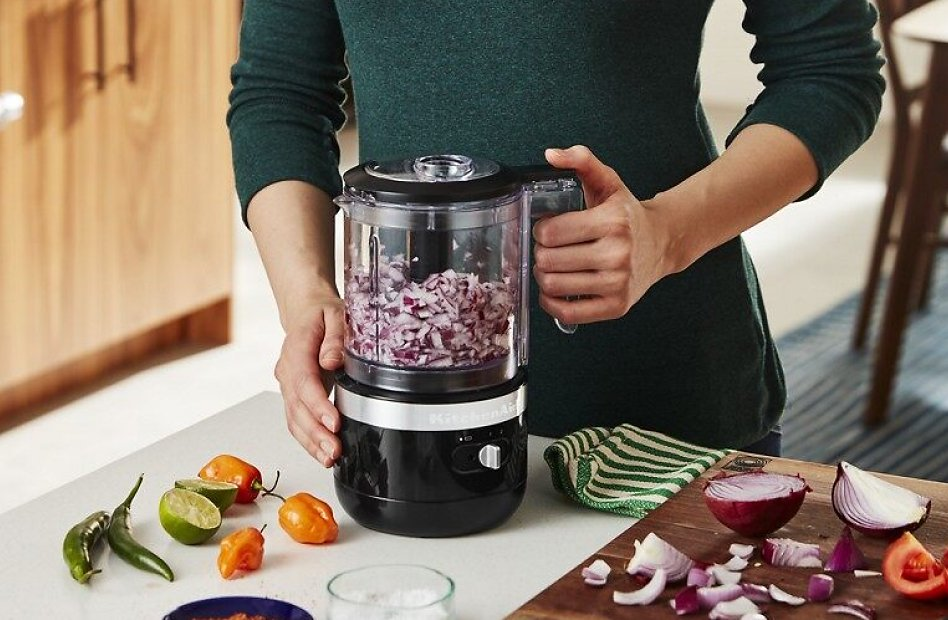 Woman chopping red onions with a black cordless food chopper