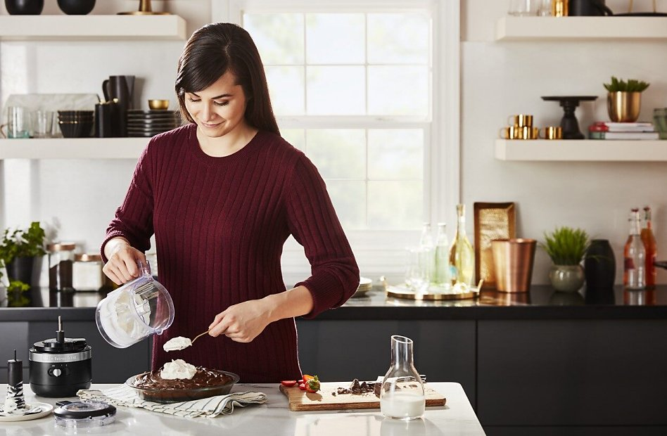 Woman spooning whipped cream from a cordless food chopper onto a chocolate pie
