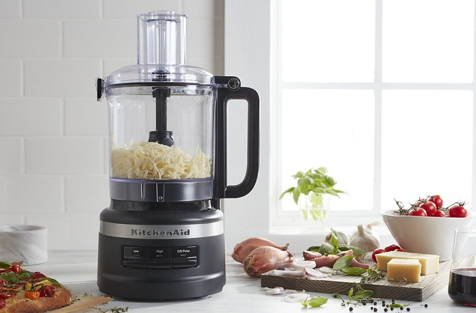 KitchenAid® food processor with shredded cheese in the work bowl.