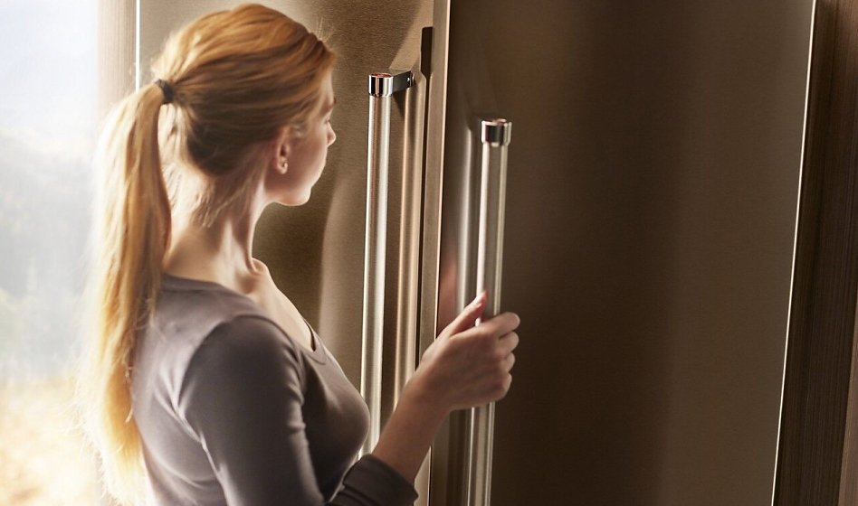 Woman looking inside a side by side or French door refrigerator