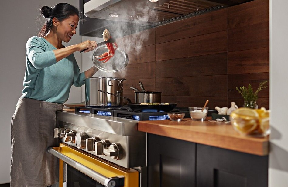 Woman cooking crab legs on a gas range