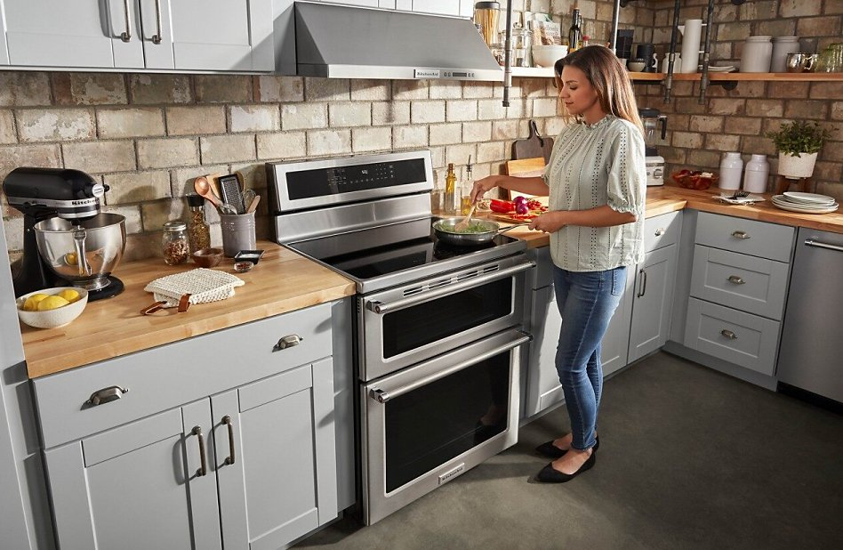 Woman stirring dish on top of a double electric range