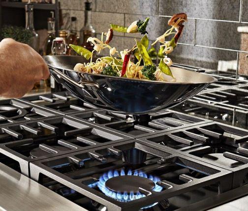 Hand flipping a stir fry in a wok