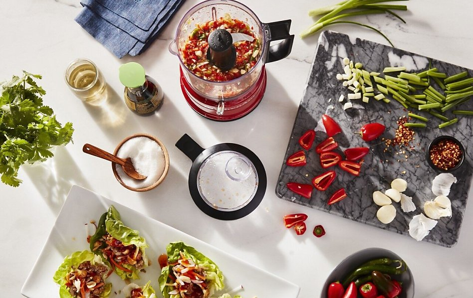 View of red KitchenAid® food processor on white counter with salsa ingredients