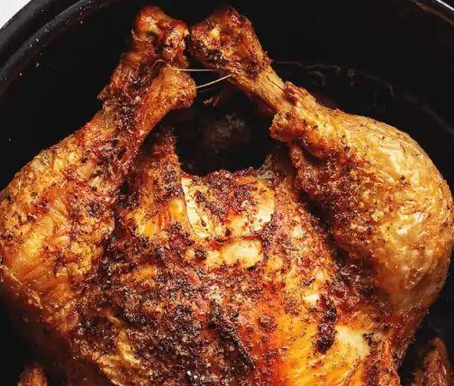 Whole roast chicken in an air fryer basket