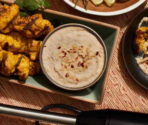 Immersion blender on table with satay chicken and sauce