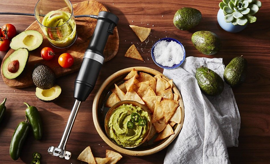 Immersion blender laying beside bowl of guacamole and chips surrounded by guacamole ingredients