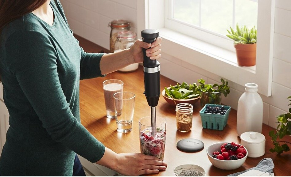 Woman blending smoothie with black KitchenAid® cordless immersion blender